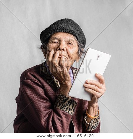 Portrait Of A Senior Woman Confused With Tablet In Vintage Costume. Isolated On Grey Background
