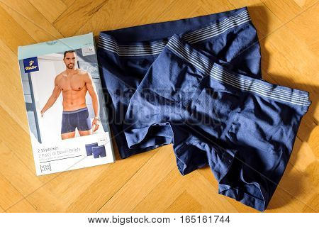 LONDON UNITED KINGDOM - NOVEMBER 5 2015: New pairs of blue male boxers brief on wooden background made by Tchibo Germany