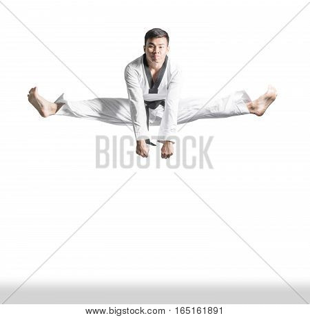 Portrait Of A Handsome Asian Man Jumping Kick With Taekwondo Black Belt . Isolated On White Backgrou