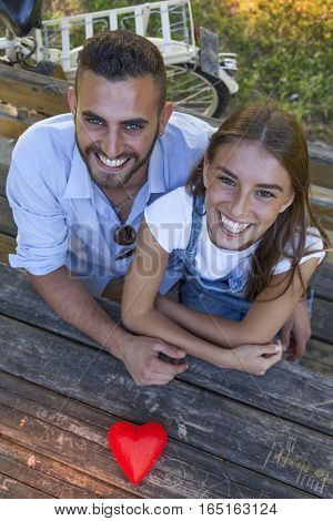 Beautiful Couple Of Young Adults Showing Heart Symbol In The Park
