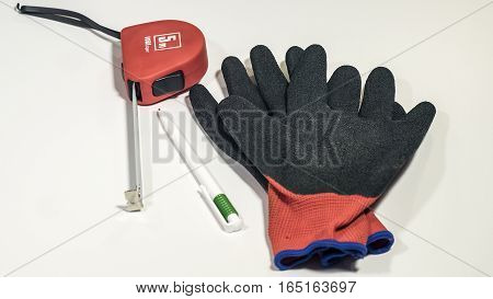 Work gloves, tape-line and pen isolated on white background