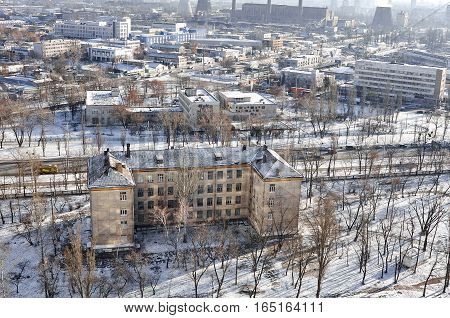 The aerial View of urban fringes in Kyiv, Ukraine in sunny winter day.View over the city rooftops with sunlight and snow at Kiev's Darnitsa suburb.Central Heating and Power Plant, moderns buildings and school at Industrial uptown