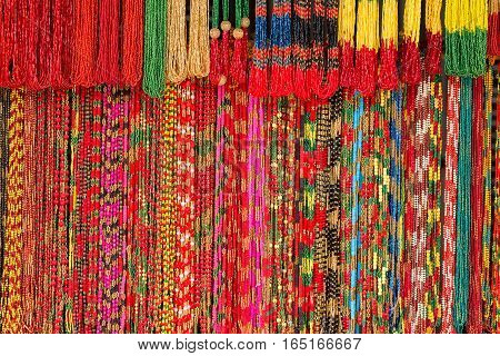 Bright background of handmade strands of colorful beads at outdoor crafts market in Kathmandu Nepal. Asian hand made souvenirs made with local craftsman and being sold at the market