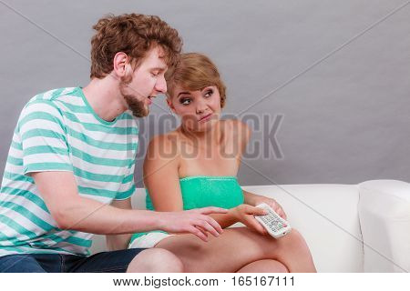 watching television - funny couple sitting on couch with remote control fighting changing channel