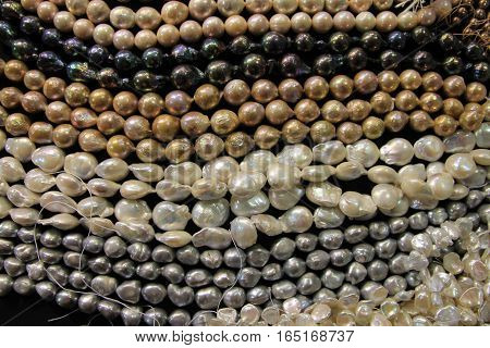 Many colorful pearl necklaces as a background