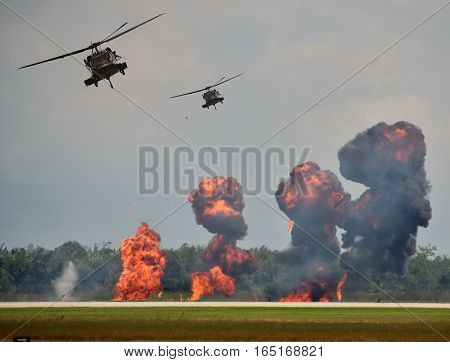 Military helicopters in ground attack with explosions