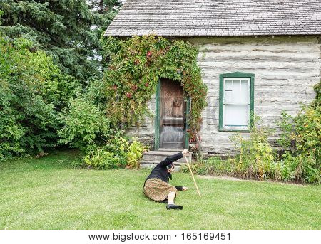 horizontal image of an elderly lady with a walking cane falling down on the grass outside the house on a summer afternoon.