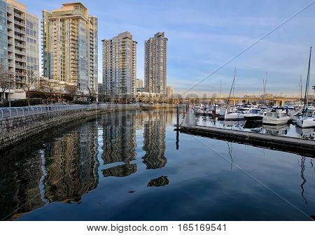 Seawall, highriser and boats. Reflection in still water. Yaletown. Cambie Bridge. False Creek. Vancouver downtown. British Columbia. Canada.
