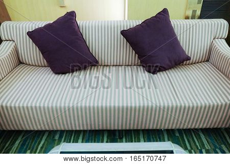 Sofa with beautiful violet pillows in the room