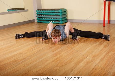 Man sitting on cross splits. Deflection forward. Stretching after a workout. Healthy lifestyle concept. Fitness.