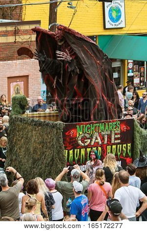 ATLANTA, GA - OCTOBER 2016:  A terrifying demonic monster rises up via hydraulics on a parade float promoting a haunted house at the annual Little Five Points Halloween parade in Atlanta GA on October 15 2016.