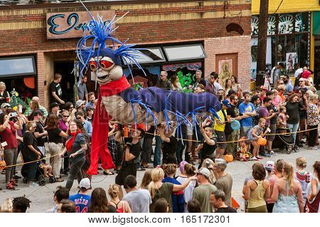 ATLANTA, GA - OCTOBER 2016:  Puppeteers carry a giant caterpillar puppet along the parade route of the annual Little Five Points Halloween parade in Atlanta GA on October 15 2016.