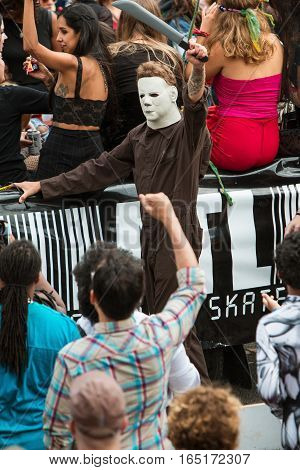 ATLANTA, GA - OCTOBER 2016:  A man wearing coveralls and a Michael Myers mask from the Halloween movie series wields a fake machete as he walks in the annual Little Five Points Halloween parade in Atlanta GA on October 15 2016.