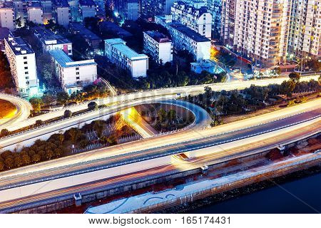 Freeway in night with cars light in modern city.