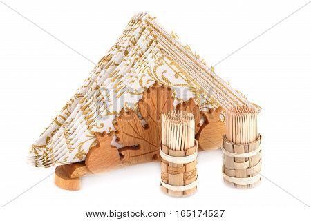 Paper napkins in wooden holder and toothpicks isolated on white background.