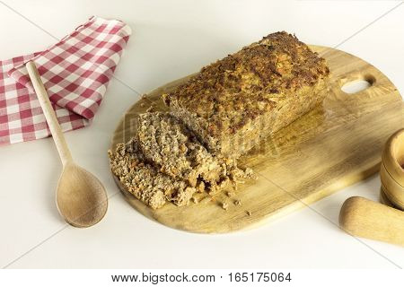 A photo of freshly cooked and cut meatloaf on a wooden board