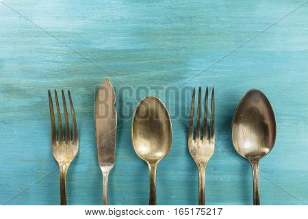 An overhead photo of vintage forks, spoons and a knife on a vibrant turquoise background texture. A restaurant menu or special offer banner design template