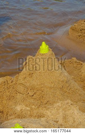 building the sandcastle on the beach near the river