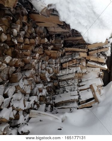 Firewood piled in the winter are stored under the snow. Firewood in snow