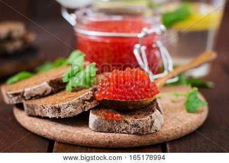 Jar With Red Caviar And Bread On Wooden Background