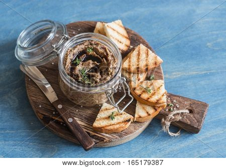 Vegetarian snack - beans and mushroom pate on wooden board on blue background