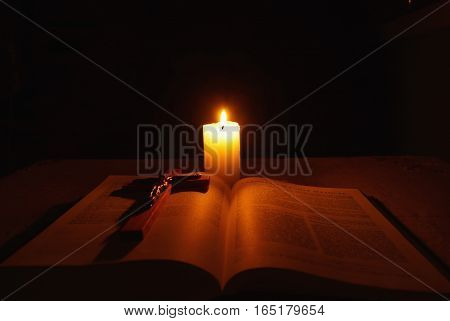 Burning candle, open Bible and wooden cross with crucifix on desk in dark.