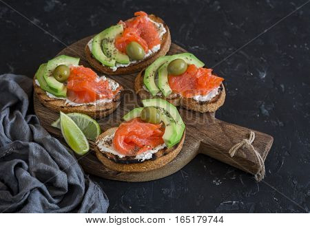 Delicious appetizers with wine - cream cheese smoked salmon and avocado sandwiches and olives on a wooden board.