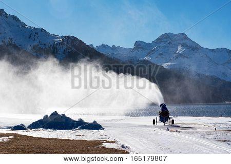 Snow canon or gun blowing artificial snow onto a piste or run at a mountain ski resort