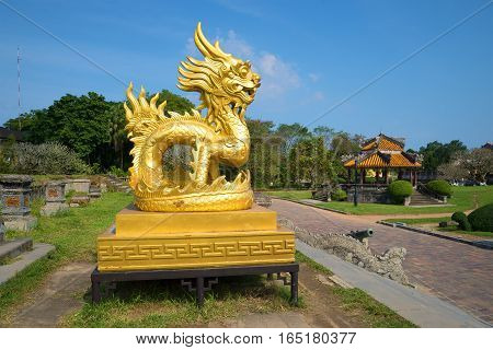 HUE, VIETNAM - JANUARY 07, 2016: A sculpture of the Gold dragon on a terrace of the forbidden imperial Purple city. The view of the profile