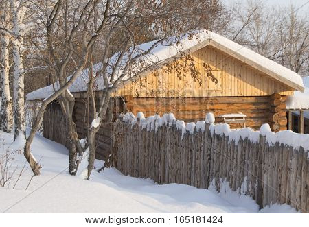 Small wooden log cabin in a snowy forest.