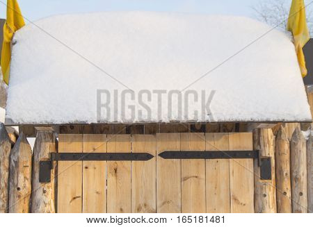 wooden gate in the fence on a Sunny winter day.