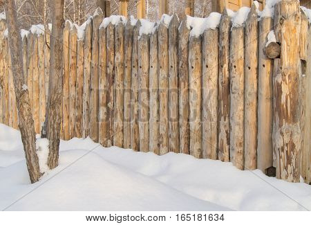 Paling, Wooden fence made of logs in the village, winter.