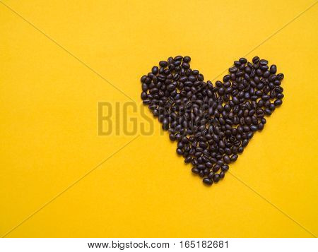 Top view of brown coffee bean arrange in heart shape on yellow background - love concept