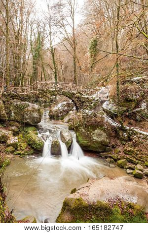 deep in the forest there is a small waterfall in switzerland in Luxembourg whit snow