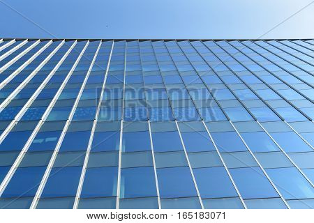 Modern office building wall made of blue glass and steel frame with blue sky