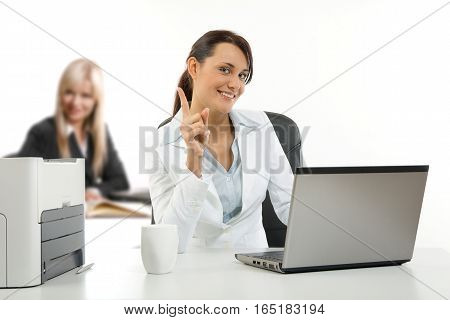 Two young women working in the office on their laptops
