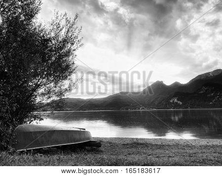 Upside Down Fishing Paddle Boat On Bank Of Alps Lake. Smooth Levelof Autumnal Lake.