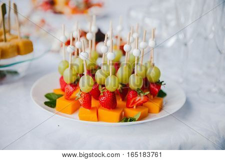 Grapes, strawberries and mango. Fruit dessert canape.