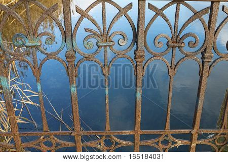 Old rusty vintage fence in front of a water. Stock image.