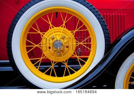 Close view of colorful wirewheel spare tire on antique car running board