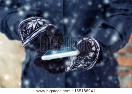 Mobile phone and female hands with winter gloves sending sms text message