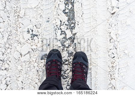 Man in winter boots standing in snow top view