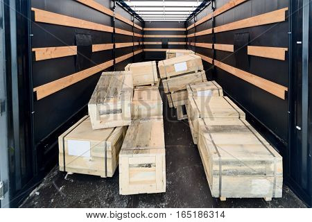Several wooden crates inside the cargo van. The boxes piled in a disorderly pile. Interior view of empty semi truck lorry