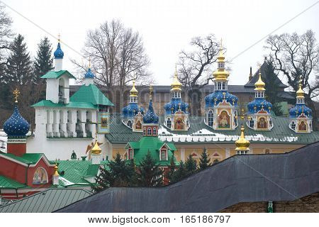 Belfry and domes of the Sacred and Uspensky Pskovo-Pechorsky monastery in the gloomy February afternoon. Pechory, Pskov region. Russia