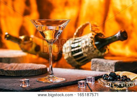 Martini glass, olives and wine bottles over fire light background