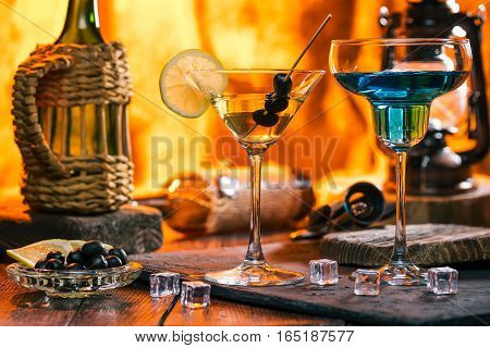Colorful cocktails in margarita and martini glasses. Wine, olives and lemon slices on bar counter. Fireplace lights on the background