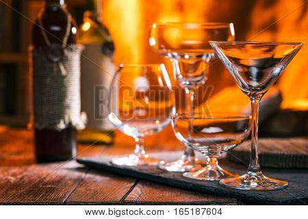 Various empty glasses for wine and cocktails. Fire on the background