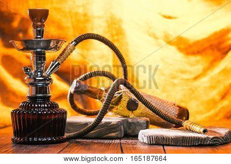 Hookah and wine bottle on wood boards over fire light