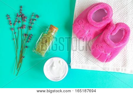 baby accessories with lavander for the bathroom on green background top view