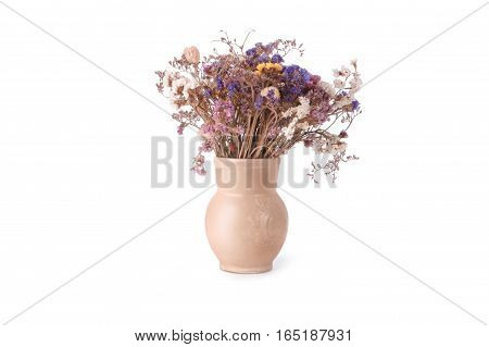 Bouquet of dried wild flowers in a light beige ceramic pot isolated on white background. Yellow, white, and blue wildflowers in ceramic pot handmade soft lighting.